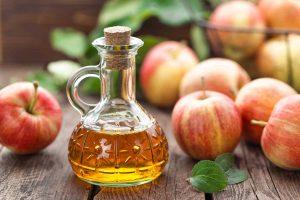 Jar of vinegar next to apples