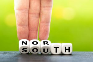 hand rolling dice that spell north and south